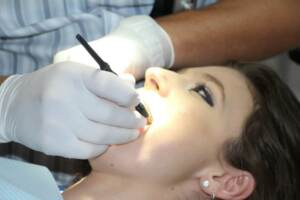 Access to Care Akron | A woman receiving a dental cleaning