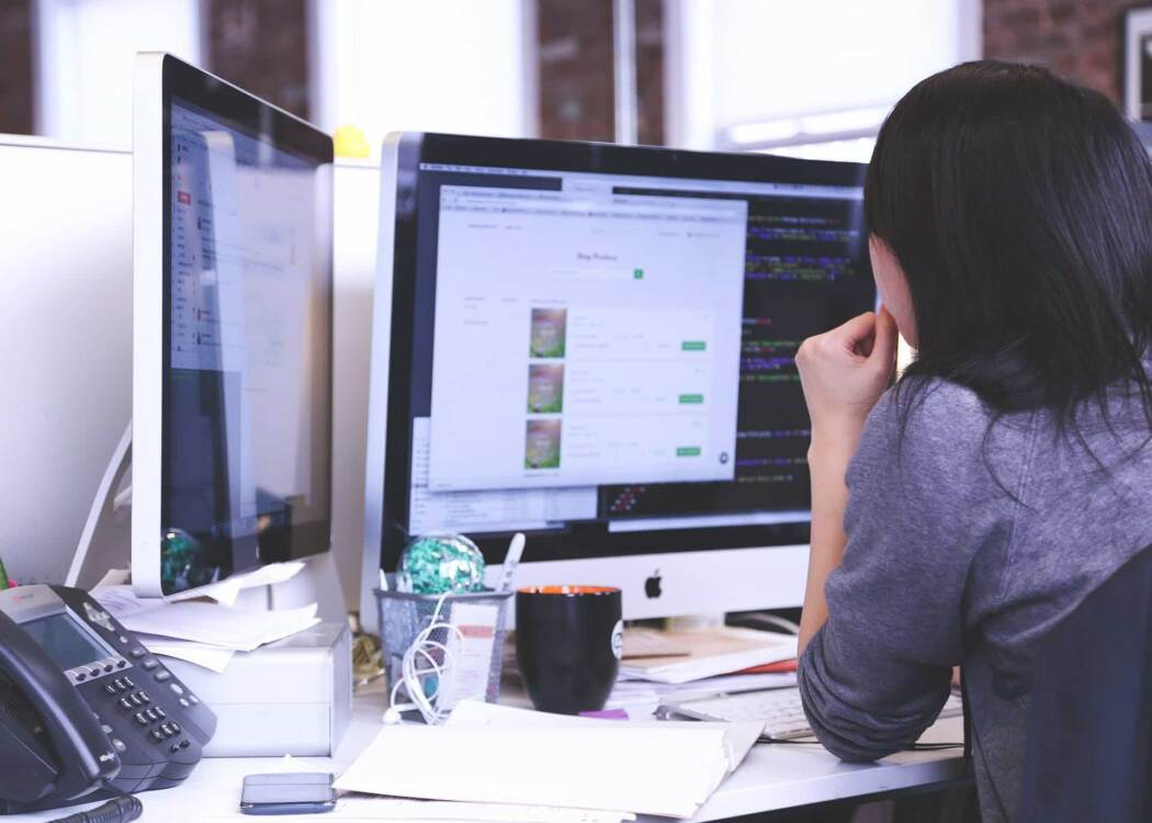 Web development services near me | Woman at desktop computer with two monitors on cluttered desk.