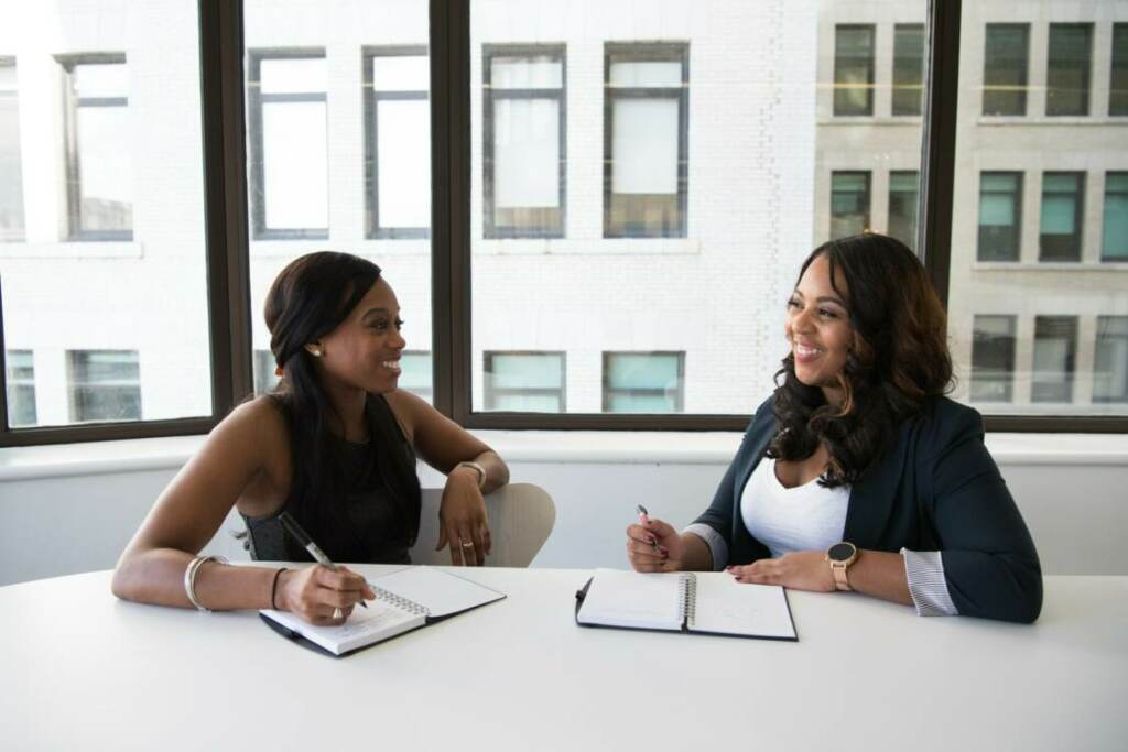 Web development services | Two women at a table smiling and talking