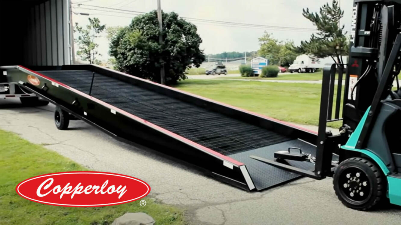 Copperloy Yard Ramp Rental | A yard ramp attached to a truck bed and a forklift preparing to travel up the ramp.