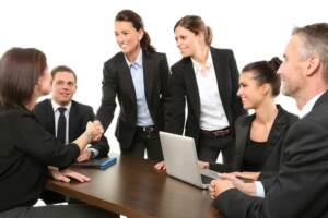 Group of business people around a desk smiling and shaking hands | Consolidated aerospace manufacturing