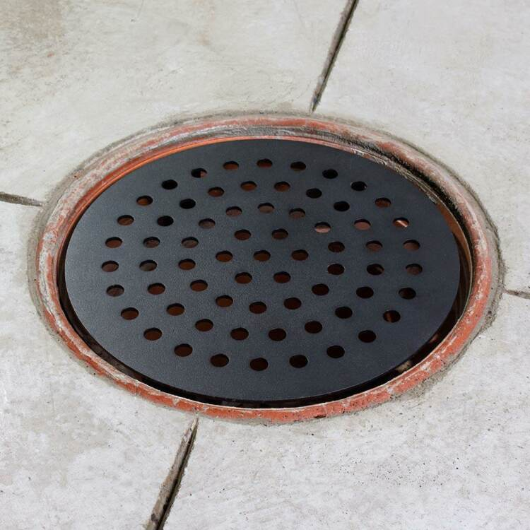 A black steel garage floor drain cover