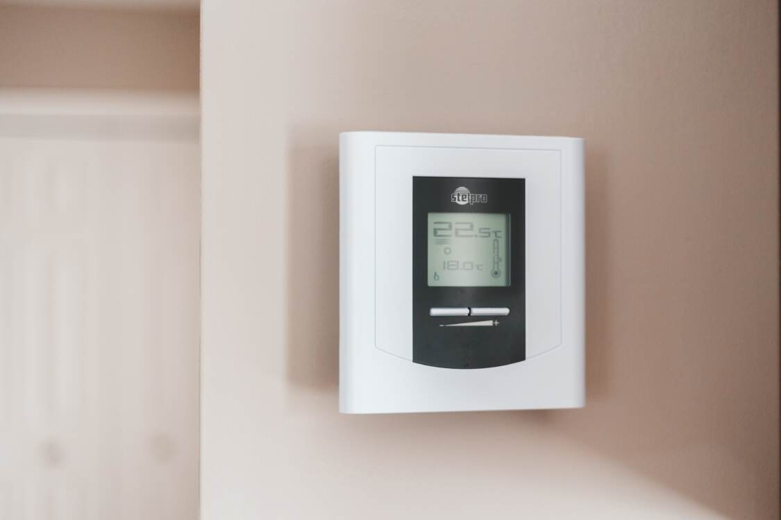 A thermostat mounted on a wall   HVAC Zoning