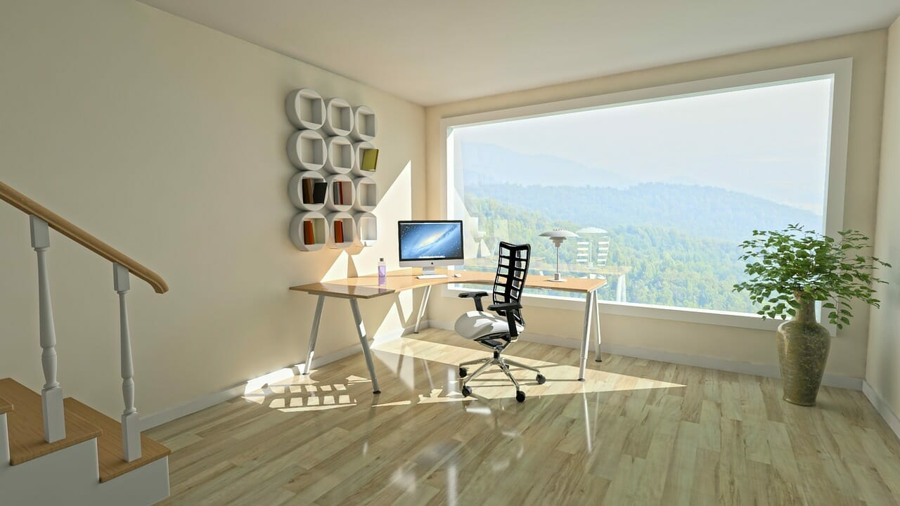 A corner desk with a computer next to a window overlooking a forest | HVAC zoning home systems