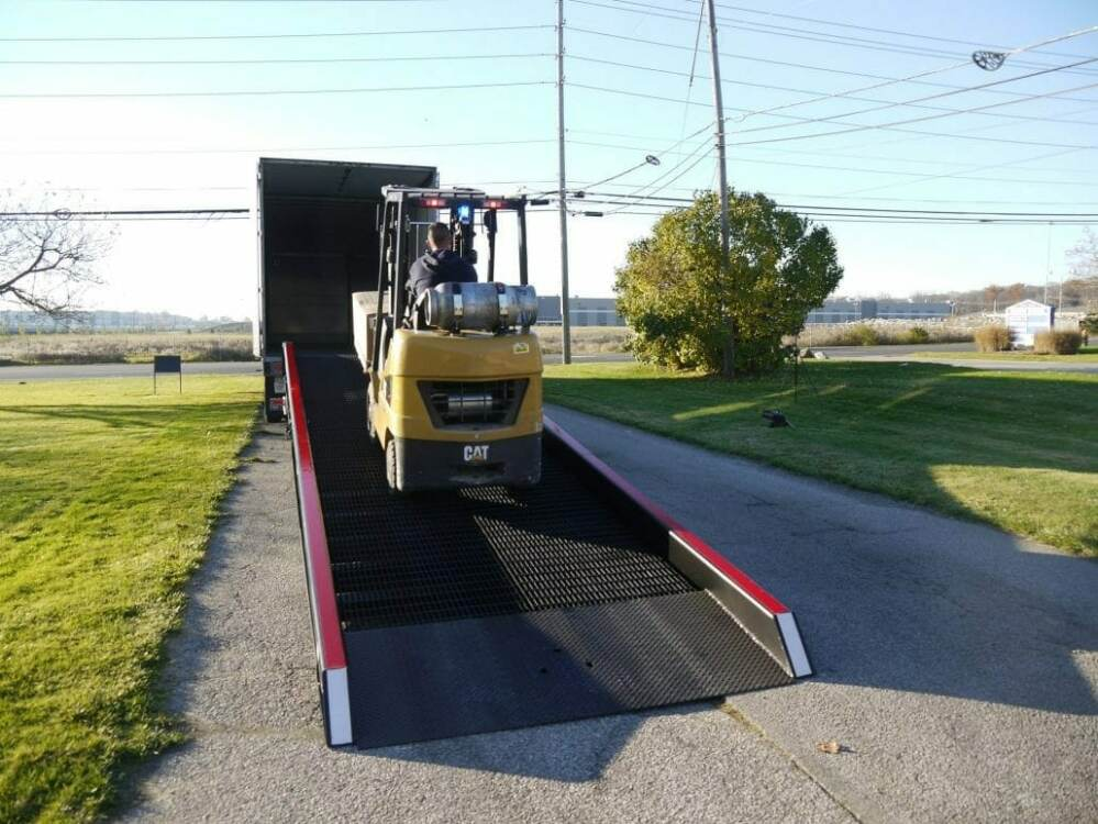 Yellow forklift traveling up a Copperloy yard ramp | Rent a ramp