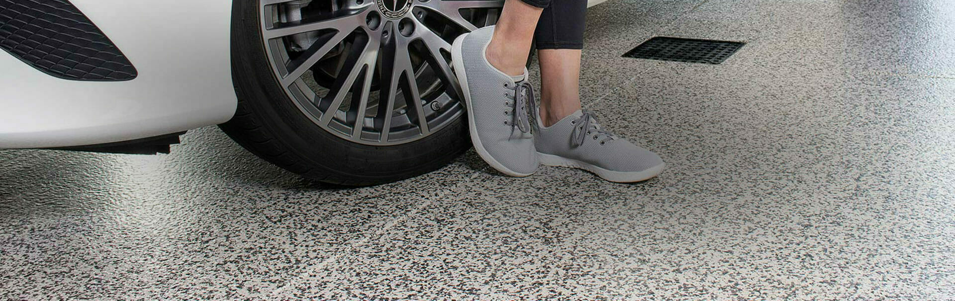 A person in tennis shoes standing next to a car on a polyaspartic floor | Polyaspartic vs epoxy