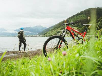 A mountain bike and person standing by a lake   Bicycle covers