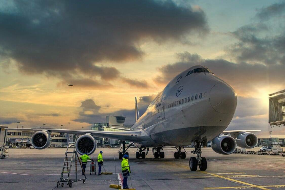 A crew standing by a parked airplane | Aircraft landing gear