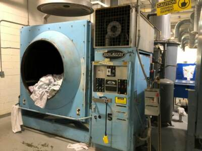 A used industrial dryer filled with laundry