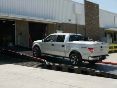 Pickup truck driving up loading dock ramp