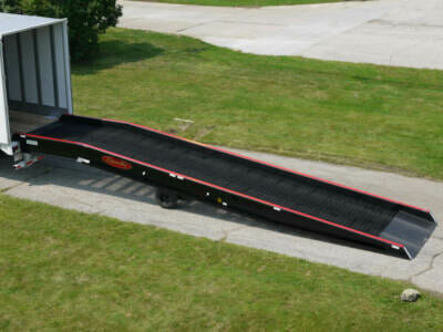 Portable loading dock ramp connected to semi trailer