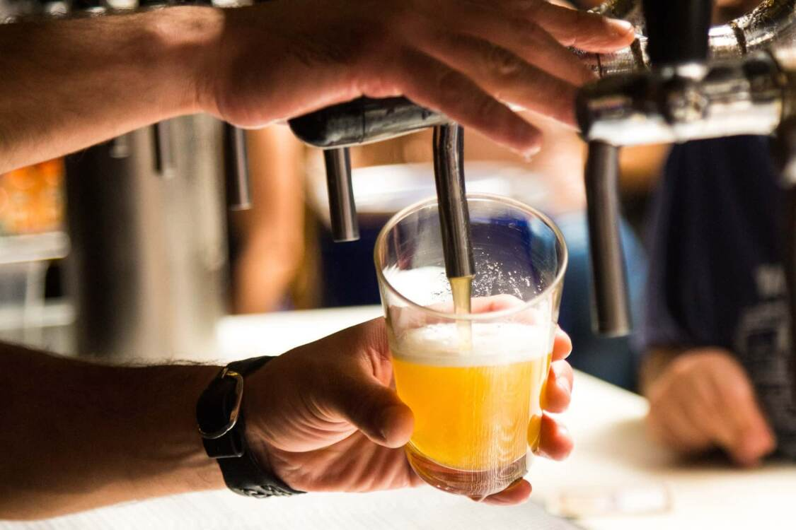 person pouring draft beer | brewery pump