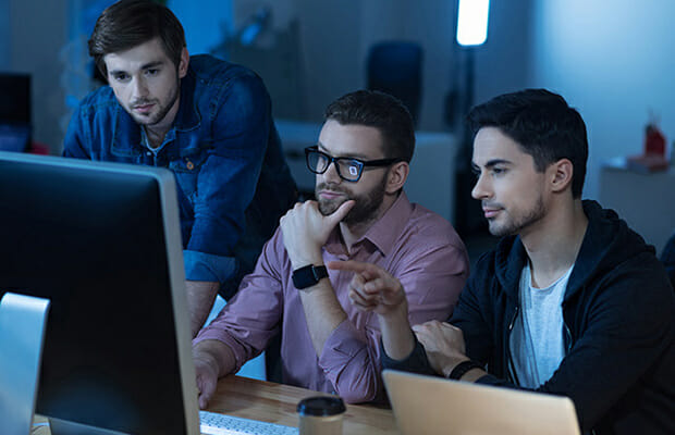 3 men sitting at a computer | Akron IT services